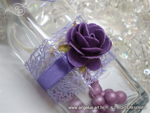 ljubičasta pozivnica u boci s ružom i mrežom